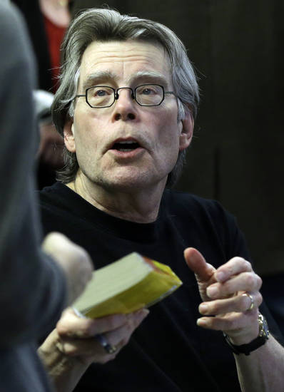 Novelist Stephen King hands back a book after signing it for a student at the University of Massachusetts-Lowell in Lowell, Mass., Friday, Dec. 7, 2012. (AP Photo/Elise Amendola)