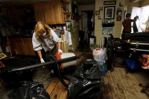 Kathleen Seemar, left, and her 13-year-old son, Andrew Seemar, clean up their home after it was flooded during superstorm Sandy, Thursday, Nov. 1, 2012, in Brick, N.J. Three days after Sandy slammed the mid-Atlantic and the Northeast, New York and New Jersey struggled to get back on their feet, the U.S. death toll climbed to more than 80, and more than 4.6 million homes and businesses were still without power.  (AP Photo/Julio Cortez) ORG XMIT: NJJC118
