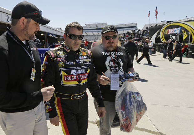 Tony Stewart, center, walks to his hauler after practice for Sunday's NASCAR Sprint Cup auto race at Martinsville Speedway in Martinsville, Va., Friday, April 5, 2013.  (AP Photo/Steve Helber)