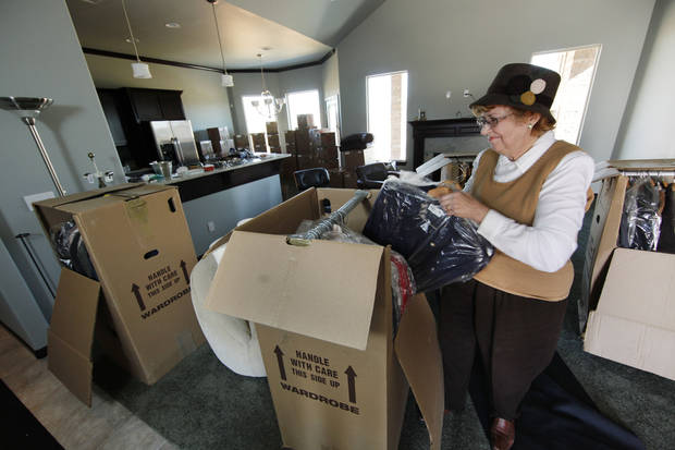 Marlene Deatherage unpacks boxes at the home she and her husband, Rich, just bought northwest of Pennsylvania Avenue and Covell Road. The retirees moved here from Michigan. Photo by Steve Gooch, The Oklahoman