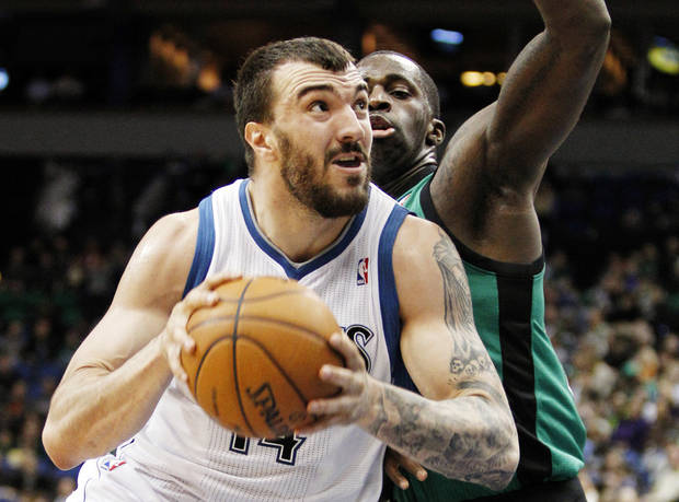 Minnesota Timberwolves center Nikola Pekovic (14) drives around Boston Celtics forward Brandon Bass for a basket during the first half of an NBA basketball game Monday, April 1, 2013, in Minneapolis. (AP Photo/Genevieve Ross)