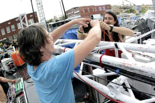 Flaming Lips multi-instrumentalist Steven Drozd (left) and roadie Zac Cox gather equipment after a lighting rig toppled onstage during the Brady District Block Party.   <strong>BY NATHAN POPPE, THE OKLAHOMAN</strong>