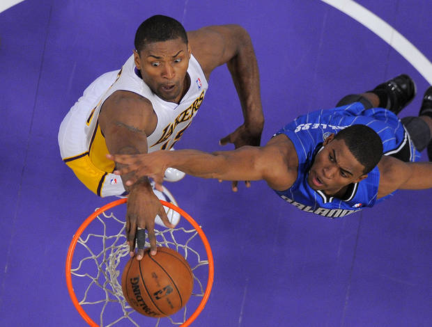 Los Angeles Lakers forward Metta World Peace, left, dunks as Orlando Magic forward Moe Harkless defends during the first half of their NBA basketball game, Sunday, Dec. 2, 2012, in Los Angeles. (AP Photo/Mark J. Terrill)