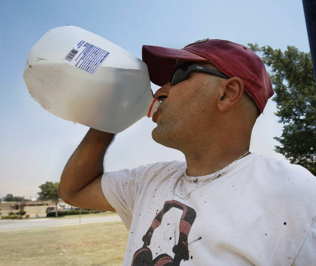 Robert Gamboa brings a gallon of frozen water to work each morning and it stays icy cold most of the day.  He is assembling a sign on 24th Ave NE as the temperature tops 100 degrees for the second day on Wednesday, June 27, 2012, in Norman, Okla.  Photo by Steve Sisney, The Oklahoman