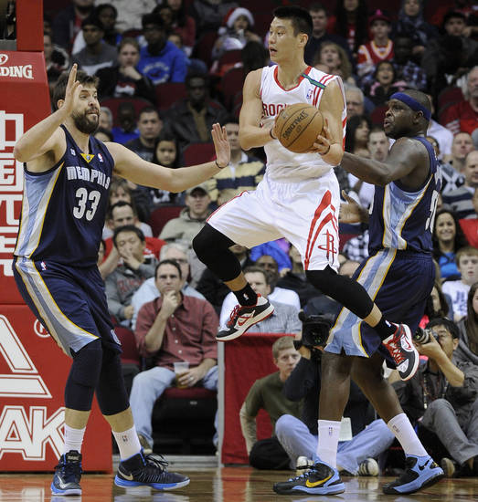 Houston Rockets' Jeremy Lin, center, looks to pass the ball between Memphis Grizzlies defenders Marc Gasol (33) and Zach Randolph (50) in the first half of an NBA basketball game on Saturday, Dec. 22, 2012, in Houston. (AP Photo/Pat Sullivan)