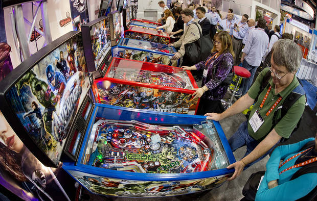 Convention goers play on a bank of pinball machines at the Consumer Electronics Show, Wednesday, Jan. 9, 2013, in Las Vegas. (AP Photo/Julie Jacobson)