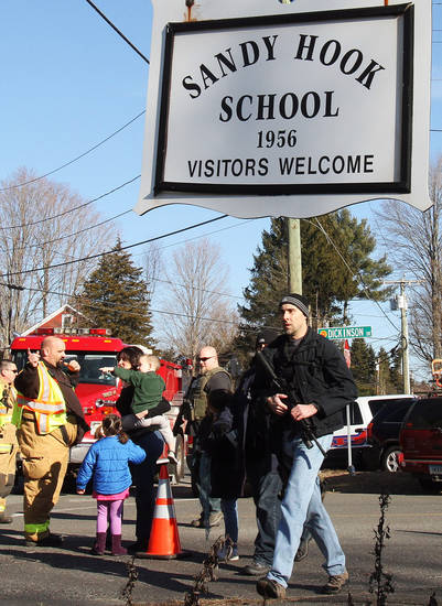 Parents walk past police and firefighters away from the Sandy Hook Elementary School with their children following a shooting at the school, Friday, Dec. 14, 2012 in Newtown, Conn. A man opened fire inside the Connecticut elementary school where his mother worked Friday, killing 26 people, including 20 children, and forcing students to cower in classrooms and then flee with the help of teachers and police. (AP Photo/The Journal News, Frank Becerra Jr.) MANDATORY CREDIT, NYC OUT, NO SALES, TV OUT, NEWSDAY OUT; MAGS OUT ORG XMIT: NYWHI121