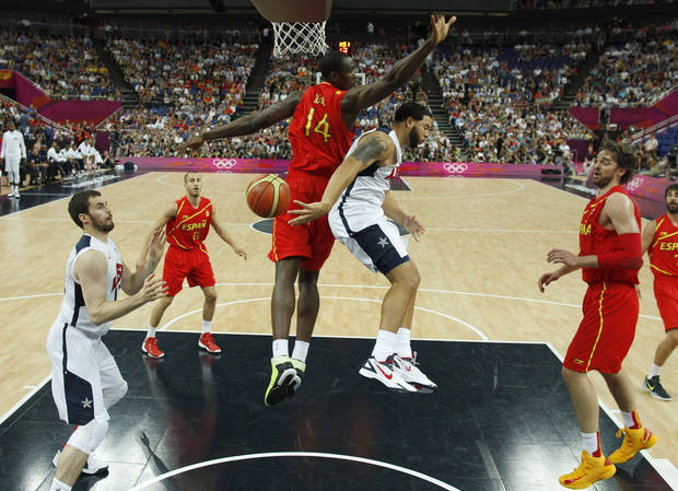 Deron Williams, second from right, of the United States makes a pass around Spain's Serge Ibaka (14) to teammate Kevin Love, left,   during their men's gold medal basketball game at the 2012 Summer Olympics on Sunday, Aug. 12, 2012, in London. (AP Photo/Sergio Perez, Pool)