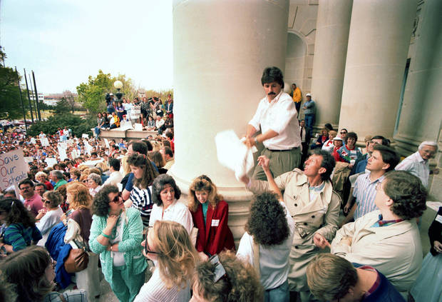 "20th ANNIVERSARY OF HB-1017. An unidentified man yanks a ""Go to Work"" sign held by Mike Myler of Moore, standing above, who was unhappy that teachers left school to demonstrate at the state Capitol. April 16, 1990. Staff Photo by Jim Beckel."