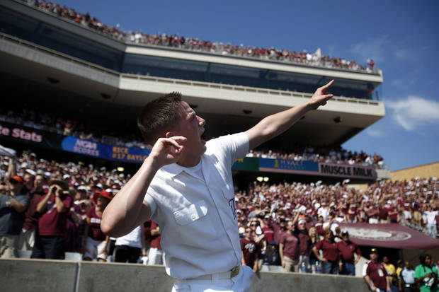 An A&M yell leader encourages the crowd in the second half of the Texas A&M-Oklahoma State game on Saturday. Photo by Sarah Phipps, The Oklahoman
