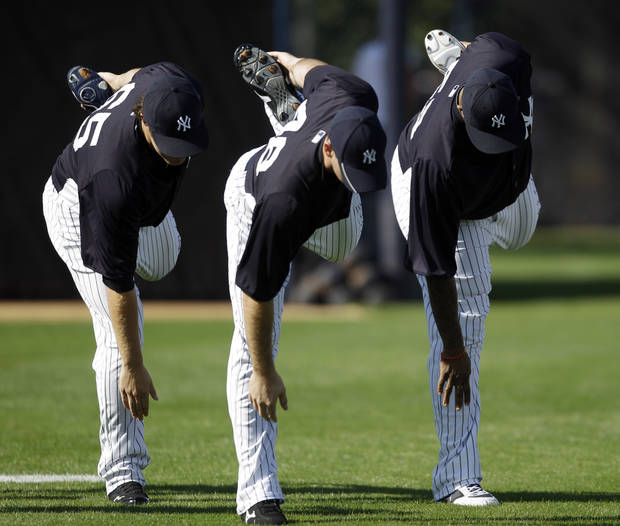 New York Yankees' Phil Hughes, from left, Boone Logan and CC Sabathia stretch during practice at baseball spring training, Monday, Feb. 20, 2012, in Tampa, Fla. (AP Photo/Matt Slocum)