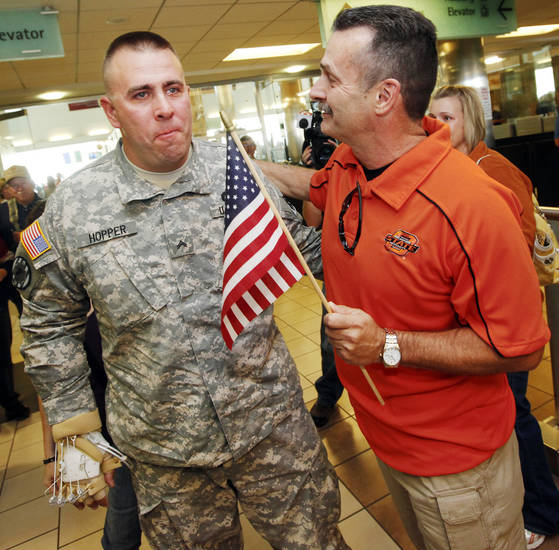 Cpl. Scott Hopper, left, reacts as he is greeted by Tom Edwards after Hopper arrived to a surprise welcome of supporters at Will Rogers World Airport in Oklahoma City,  Friday, Oct. 28, 2011. Cpl. Scott Hopper is a Payne County sheriff's deputy who has returned to Oklahoma to attend OSU's homecoming. Edwards, also a Payne County sheriff's deputy, and Hopper were partners before Hopper left for Afghanistan with the National Guard. Hopper was injured in Afghanistan and has been recovering in a San Antonio hospital. Photo by Nate Billings, The Oklahoman