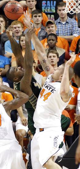 Oklahoma State 's Philip Jurick (44) defends a shot by South Florida Bulls' Toarlyn Fitzpatrick (32) during the college basketball game between Oklahoma State University (OSU) and the University of South Florida (USF) on Wednesday , Dec. 5, 2012, in Stillwater, Okla.   Photo by Chris Landsberger, The Oklahoman