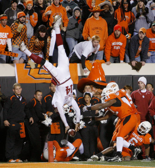 OU's Sam Bradford is flipped out of bounds by OSU's Orie Lemon during the second half of the college football game between the University of Oklahoma Sooners (OU) and Oklahoma State University Cowboys (OSU) at Boone Pickens Stadium on Saturday, Nov. 29, 2008, in Stillwater, Okla. STAFF PHOTO BY CHRIS LANDSBERGER