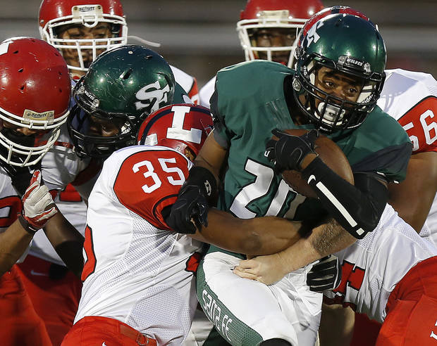 Edmond Santa Fe's Cameron Westbrook  tries to fight off Lawton's Neville Abram during their high school football game at Wantland Stadium in Edmond, Okla., Thursday, October 11, 2012. Photo by Bryan Terry, The Oklahoman