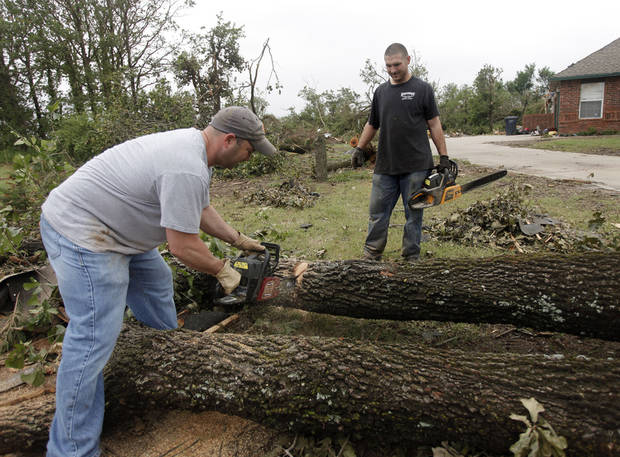 Dustin Moss, left, and Rory Farmer use chain saws to cut up damaged trees in the Dripping Springs Estates Saturday, May 15, 2010. Saturday hundreds of volunteers went into areas that had been affected by last week's tornadoes to help clear debris. Photo by Doug Hoke, The Oklahoman.