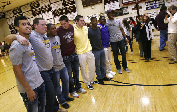 Members of the Jenks high school football team including Taylor Hunter (left), Brandon Waggoner, Braden Calip, Garrett Patterson, Nick Lucido, Trey&#039;vonne Barre, Jeff Scallion, and Jordan Smallwood pose for a photo for family and friends during signing day in Jenks, Okla., on February 6,2013. JAMES GIBBARD/Tulsa World