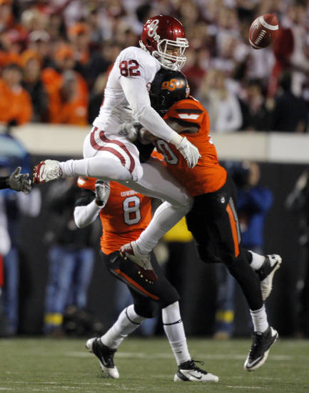 Oklahoma State's Markelle Martin (10) hits  Oklahoma's James Hanna (82) as he tries to catch the ball during the Bedlam college football game between the Oklahoma State University Cowboys (OSU) and the University of Oklahoma Sooners (OU) at Boone Pickens Stadium in Stillwater, Okla., Saturday, Dec. 3, 2011. Photo by Sarah Phipps, The Oklahoman