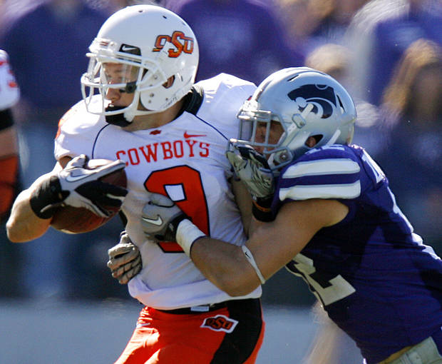 Oklahoma State's Bo Bowling (9) is hit by Kansas State's Ty Zimmerman (12) during the first half of the college football game between the Oklahoma State University Cowboys (OSU) and the Kansas State University Wildcats (KSU) on Saturday, Oct. 30, 2010, in Manhattan, Kan.   Photo by Chris Landsberger, The Oklahoman