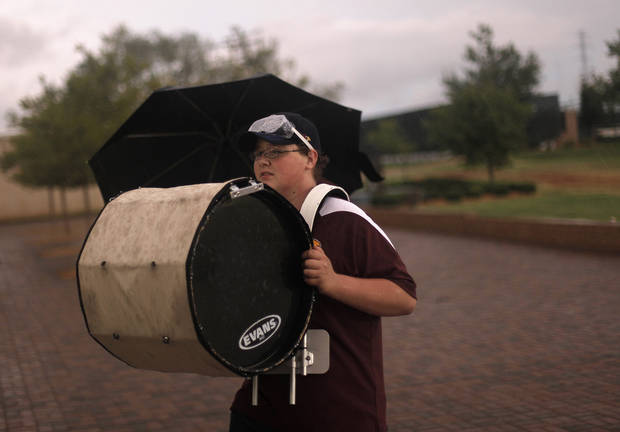 Andrew Ringer, a sophomore at Clinton High School, carries his drum out of the rain before a high school football game between Heritage Hall and Clinton in Oklahoma City, Friday, Sept. 7, 2012.  The game was delayed due to lightning.  Photo by Garett Fisbeck, The Oklahoman