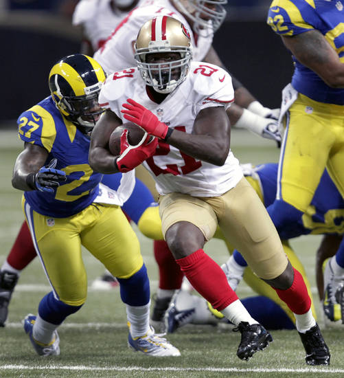 San Francisco 49ers running back Frank Gore (21) gets past St. Louis Rams free safety Quintin Mikell on his way to a 23-yard gain during the first quarter of an NFL football game on Sunday, Dec. 2, 2012, in St. Louis. (AP Photo/Tom Gannam)