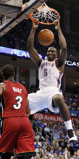 Oklahoma City's Kendrick Perkins (5) dunks the ball over Miami's Dwyane Wade (3) during the NBA basketball game between the Miami Heat and the Oklahoma City Thunder at Chesapeake Energy Arena in Oklahoma City, Sunday, March 25, 2012. Oklahoma City won, 103-87. Photo by Nate Billings, The Oklahoman