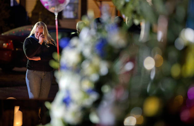 A mourner wipes a tear while visiting a memorial to the victims of the Sandy Hook Elementary School shooting at the school's entrance, Monday, Dec. 17, 2012, in Newtown, Conn. (AP Photo/David Goldman) ORG XMIT: CTDG123