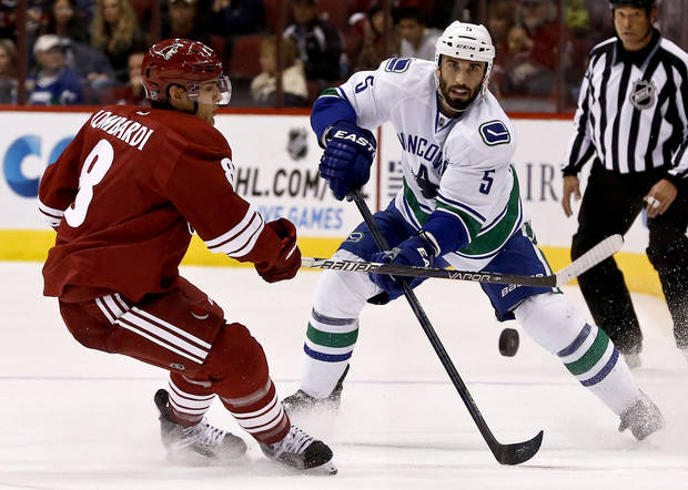 Vancouver Canucks' Jason Garrison (5) passes the puck in front of Phoenix Coyotes' Matthew Lombardi, left, during the first period in an NHL hockey game on Thursday, March 21, 2013, in Glendale, Ariz. (AP Photo/Ross D. Franklin)