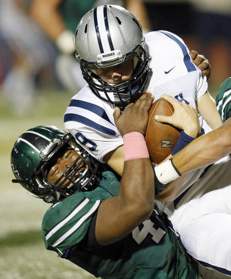 Norman North's Justin Martin (45) brings down Edmond North quarterback Luke Hoskins (9) on a keeper during a high school football game between Edmond North and Norman North in Norman, Okla., Thursday, Oct. 11, 2012. Photo by Nate Billings, The Oklahoman