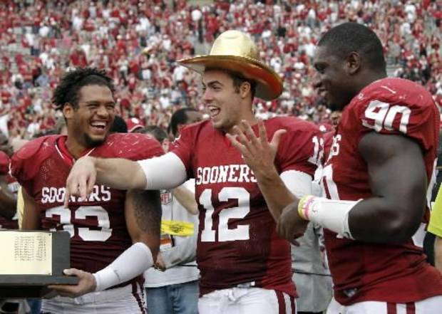 OU's Landry Jones (12) wears the Golden Hat Trophy with teammates OU's Trey Millard (33) and David King (90) during the Red River Rivalry at the Cotton Bowl in Dallas, Saturday, Oct. 13, 2012. Photo by Chris Landsberger, The Oklahoman