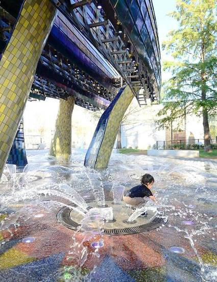 A child splashes in the Childrens Thunderstorm Fountain, one of many new attractions in the renovated Myriad Gardens.  PHOTO PROVIDED