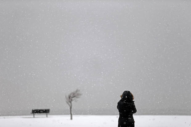 A person watches as the snow falls at Lake Hefner in Oklahoma City, Tuesday, Feb., 12, 2013. Photo by Bryan Terry, The Oklahoman