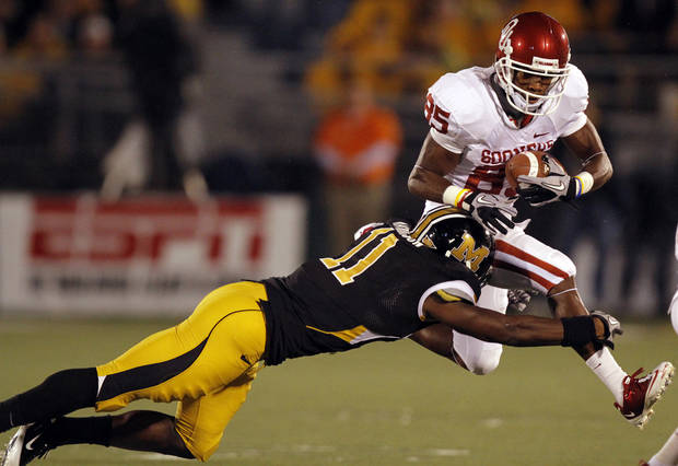 Oklahoma's Ryan Broyles (85) tries to leap past Missouri's Jarrell Harrison (11) during the first half of the college football game between the University of Oklahoma Sooners (OU) and the University of Missouri Tigers (MU) on Saturday, Oct. 23, 2010, in Columbia, Mo.  Photo by Chris Landsberger, The Oklahoman