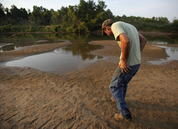 Johnny Heskett looks at hog tracks during a hunting trip near Indianola, Okla., Friday, July 6, 2012.  Photo by Garett Fisbeck, The Oklahoman