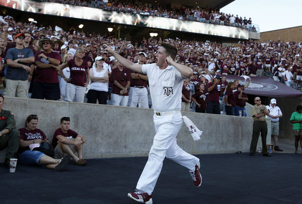 An A&M yell leader encourages the crowd in the second half of the Aggies game vs. Oklahoma State on Saturday in College Station, Texas. Photo by Sarah Phipps, The Oklahoman