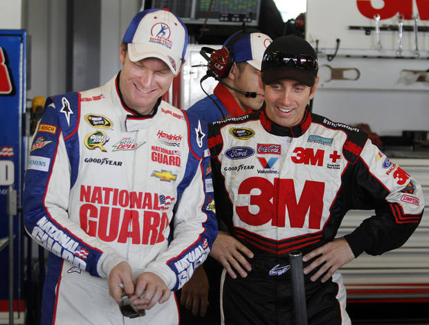 Dale Earnhardt Jr., left, and Greg Biffle share a laugh in the garage during practice for the Quaker State 400 at the Kentucky Speedway in Sparta, Ky., Friday, June28, 2013. (AP Photo/James Crisp)