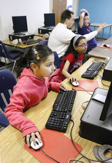 Left: Aleena Zachariah, 8, a second-grader at Skyview Elementary in Yukon, works at her computer.