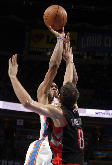 Oklahoma City's Russell Westbrook (0) shoots over Toronto's Jose Calderon (8) during the NBA basketball game between the Oklahoma City Thunder and the Toronto Raptors at Chesapeake Energy Arena in Oklahoma City, Sunday, April 8, 2012. Photo by Sarah Phipps, The Oklahoman.