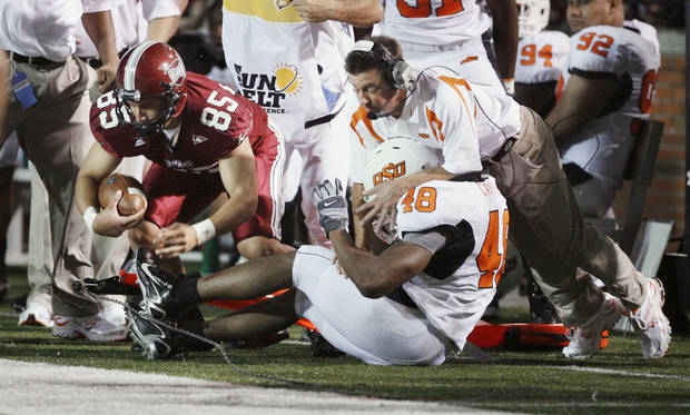 Head coach Mike Gundy is run over by Zach Carter (48) as he stops a fake punt by Adrian Vera in first half action during the college football game between the Troy University Trojans and the Oklahoma State University Cowboys at Movie Gallery Veterans Stadium in Troy, Ala., Friday, September 14, 2007. BY STEVE SISNEY, THE OKLAHOMAN