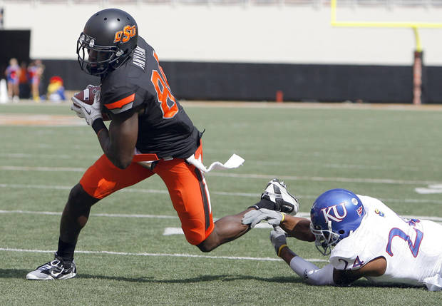 Oklahoma State's Hubert Anyiam (84) gets by Kansas' Bradley McDougald (24) on the way to a touchdown during the first half of the college football game between the Oklahoma State University Cowboys (OSU) and the University of Kansas Jayhawks (KU) at Boone Pickens Stadium in Stillwater, Okla., Saturday, Oct. 8, 2011. Photo by Sarah Phipps, The Oklahoman    ORG XMIT: KOD