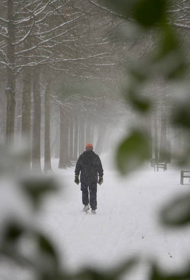 A man walks down a snowy path in the park in Wilrijk, Belgium on Tuesday, March 12, 2013. An overnight snowfall on Monday evening snarled rush hour traffic on Tuesday morning. (AP Photo/Virginia Mayo)