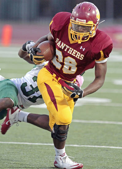 PUTNAM NORTH / Putnam City North's Devin Colbert (28) runs as Adim Chukwurah (31) hangs on as the Panthers play the Norman North Timberwolves  on Friday, October 7, 2011, in Oklahoma City, Okla.   Photo by Steve Sisney, The Oklahoman ORG XMIT: KOD