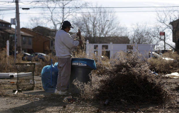 Javier Moran cleans an empty lot filled with debris from Superstorm Sandy in Staten Island, New York, Thursday, Jan. 10, 2013. The November storm damaged or destroyed 305,000 housing units in New York and more than 265,000 businesses were disrupted in the state. (AP Photo/Seth Wenig)