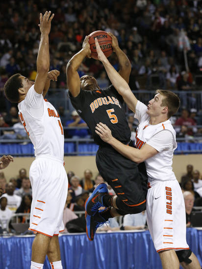Douglass' Stephen Clark drives to the basket between Seth Youngblook, left, and Corey Whisenant during the 4a boys championship game where the Douglass high school Trojans play the Roland Rangers at the State Fair Arena on Saturday, March 9, 2013 in Oklahoma City, Okla.  Photo by Steve Sisney, The Oklahoman