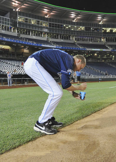 North Carolina's Chris McCue collects dirt from TD Ameritrade Park as a memento after losing 4-1 to UCLA in an NCAA College World Series baseball game in Omaha, Neb., Friday, June 21, 2013. (AP Photo/Eric Francis)