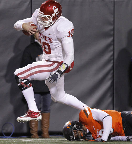 Oklahoma's Blake Bell (10) runs past Oklahoma State's Daytawion Lowe (8) for a touchdown during the Bedlam college football game between the Oklahoma State University Cowboys (OSU) and the University of Oklahoma Sooners (OU) at Boone Pickens Stadium in Stillwater, Okla., Saturday, Dec. 3, 2011. Photo by Chris Landsberger, The Oklahoman