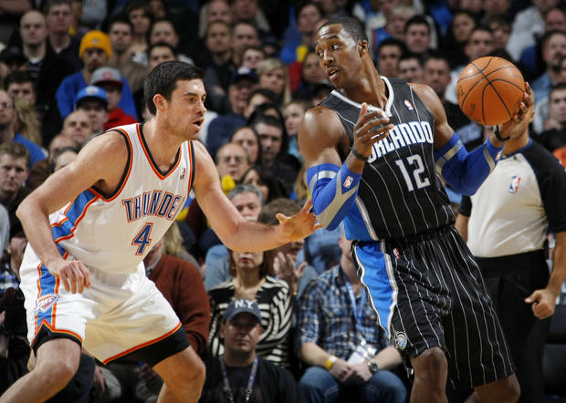 Dwight Howard (12) of Orlando looks to get around the defense of Oklahoma City's Nick Collison (4) during the NBA basketball game between the Orlando Magic and Oklahoma City Thunder in Oklahoma City, Thursday, January 13, 2011. Photo by Nate Billings, The Oklahoman