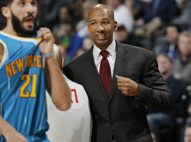 New Orleans Hornets head coach Monty Williams, right, talks over a call with referee Joey Crawford, center, as Hornets guard Greivis Vasquez (21) heads back to defend against the Denver Nuggets in the first quarter of an NBA basketball game in Denver, Friday, Feb. 1, 2013. (AP Photo/David Zalubowski)