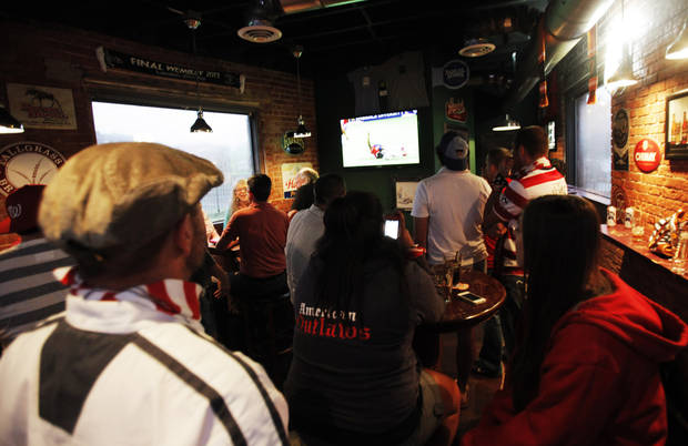 Members of the United States National Team support group the American Outlaws gather around a television in Skinny Slim's Public House in Bricktown to watch the United States take on Costa Rica on July 16, 2013.