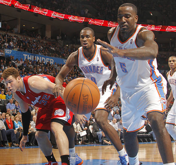 Oklahoma City Thunder center Kendrick Perkins (5) goes after a loose ball in front of Los Angeles Clippers power forward Blake Griffin (32) and Oklahoma City Thunder power forward Serge Ibaka (9) during the NBA basketball game between the Oklahoma City Thunder and the Los Angeles Clippers at Chesapeake Energy Arena on Wednesday, March 21, 2012 in Oklahoma City, Okla.  Photo by Chris Landsberger, The Oklahoman